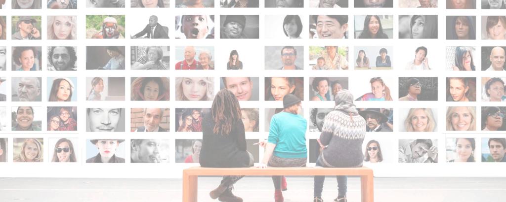 3 Menschen sitzen auf einer Bank vor einer Wand mit Portraits