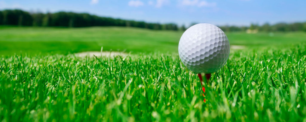 Golfball auf Tee im hohen Grün